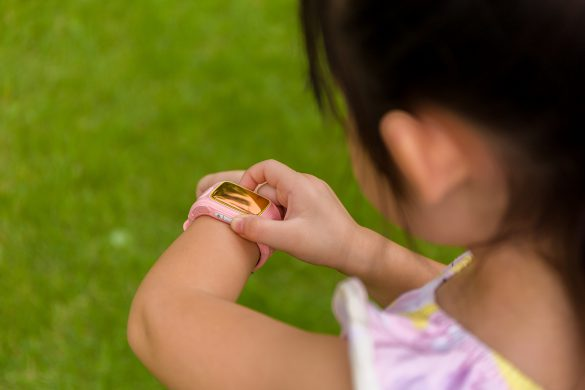 Child standing in garden using smartwatch or smart watch on her wrist.